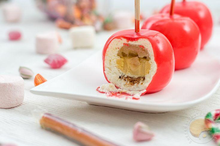 Entremets individuels en forme de pommes composés de ganache montée à la vanille, d'un insert de crémeux au caramel, d'une compotée de pommes, d'une base croustillante au spéculoos et d'un biscuit moelleux à l'amande, le tout nappé d'un glaçage miroir rouge.
