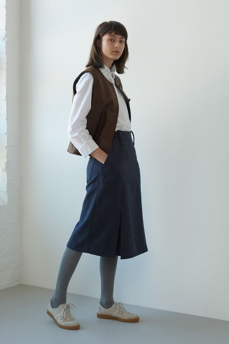 AUTUMN WINTER 2017 – DIESEL BROWN COW HIDE COALMANS JERKIN, OPTIC WHITE SOFT COTTON HOPSACK ASYMMETRIC COLLARED SHIRT, BLUE WOOL COTTON SERGE KICK PLEAT SKIRT, SILVER COTTON RIB TIGHTS, PUTTY NUBUCK ARMY TRAINER