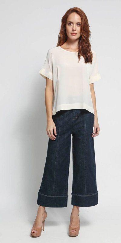 Calça pantacourt jeans, shape solto, bolsos laterais e traseiros , costura aparente, fechamento no cós com botão metalizado.