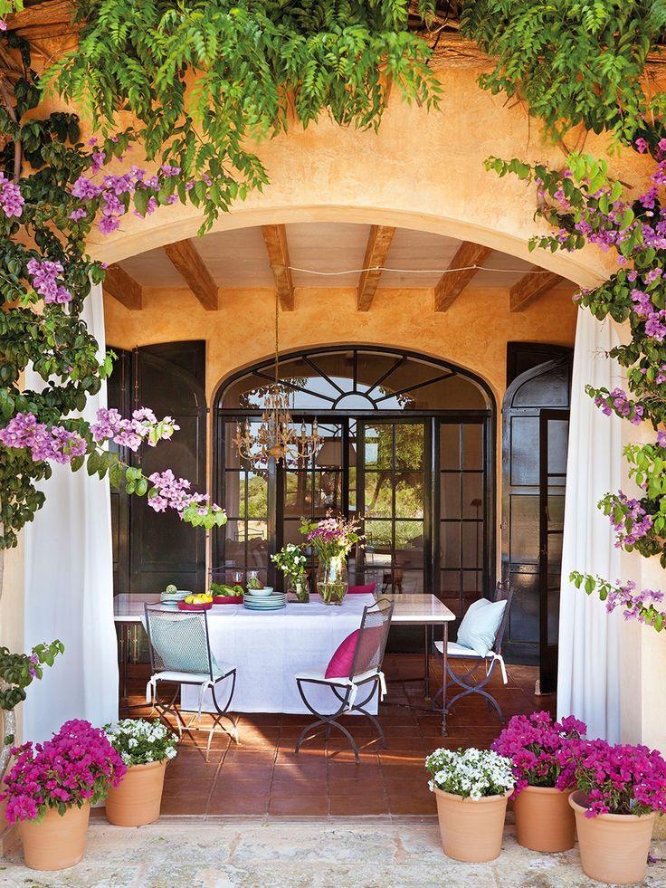 Porche con arcos con cortinas blancas rodeado de plantas