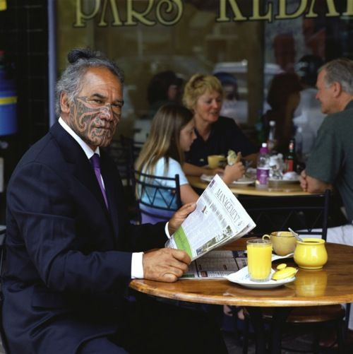 An older Maori man wearing a business suit with a purple tie has his long hair up and has traditional facial tattoos covering from his temples down.