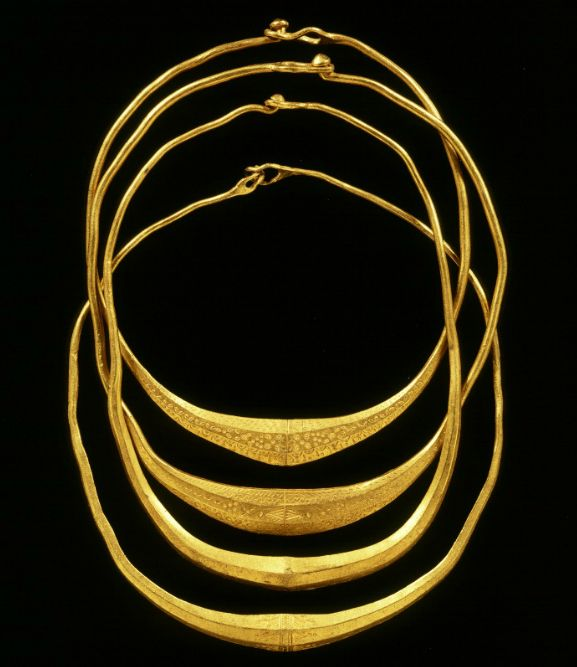 """Four solid gold necklaces found in the floodplains of the Gelderland IJssel near Olst. The neck rings may be made ​​of melted Late Roman gold coins, 'solidi'. The decorations on the jewelry are simple and a typical Germanic style. The gold is extremely fine, no less than 22 karat. This jewelry may have belonged to prominent Germanic chieftains who had contact with the Roman Empire. Here they may have sacrificed their neck rings in the river to the gods, ca. 400 A.D."""