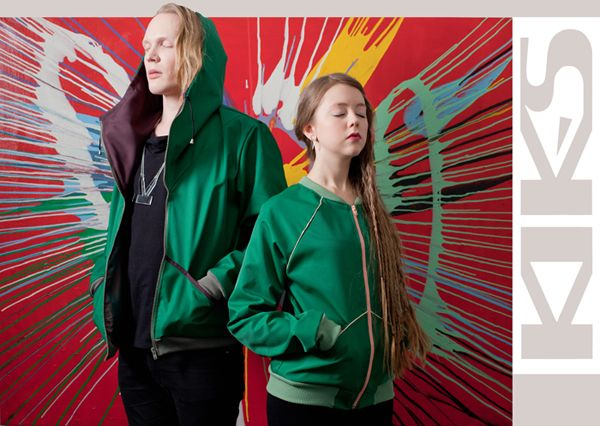 Lauri and Hilla wearing Acts II and Hits jackets in green  - on the background Konsta Koivisto's painting exploding with colors!