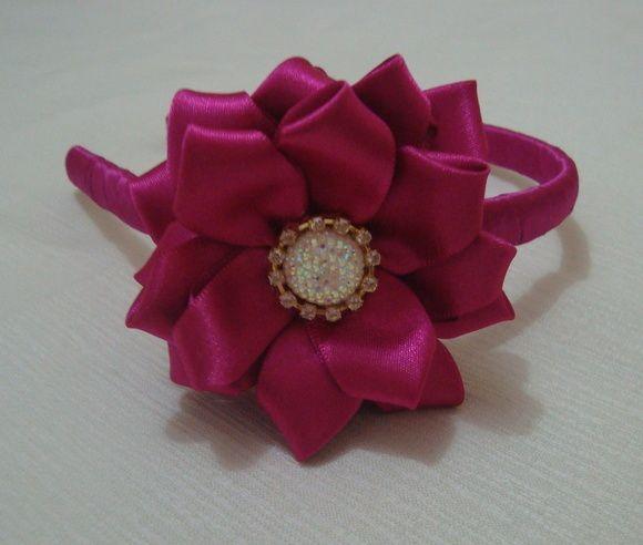 Tiara revestida em fita cetim com flor e detalhes de strass com botão chaton. R$ 18,90