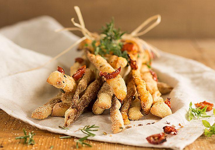 Receta de grissini torinesi con tomates secados al sol, semillas y hierbas aromáticas. Receta originaria de la zona de Turín en Italia