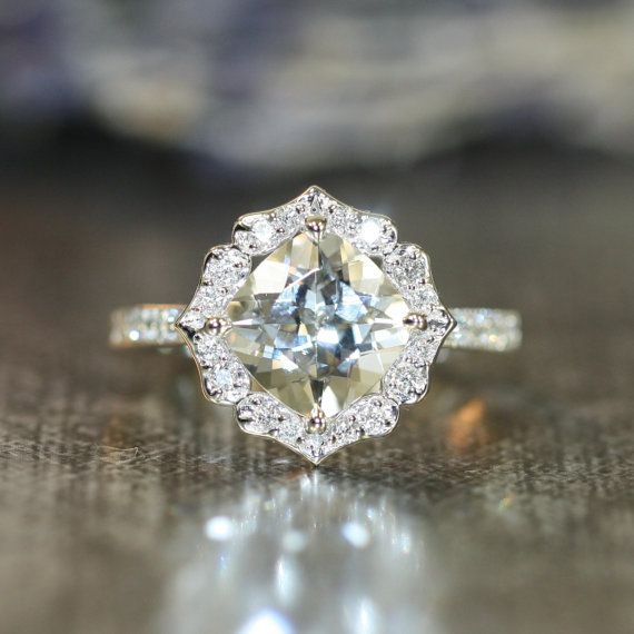 This elegant floral engagement ring features a 8x8mm cushion cut natural white topaz crafted in a solid 14k white gold vintage floral diamond