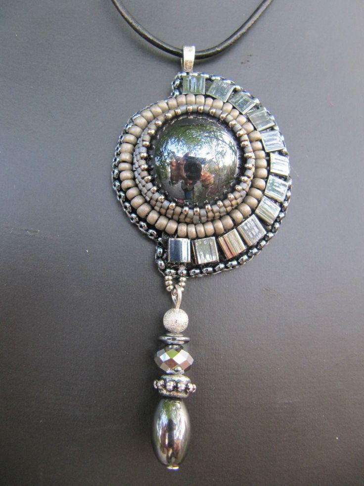 Asymmetrical hematite pendant mounted on a black leather cord.