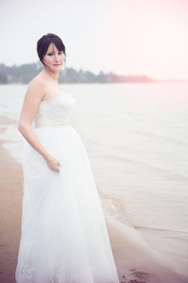 Beautiful woman in wedding dress photographed a cold winter day near lake Vänern, Sweden.