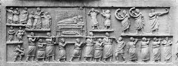 Sarcofago da Amiternum, I secolo a.C., scultura in pietra calcarea, Museo Nazionale d'Abruzzo. Presenti elementi di arte plebea arcaicizzante, evidente nella composizione su registri sovrapposti. I personaggi sono goffi e non proporzionati