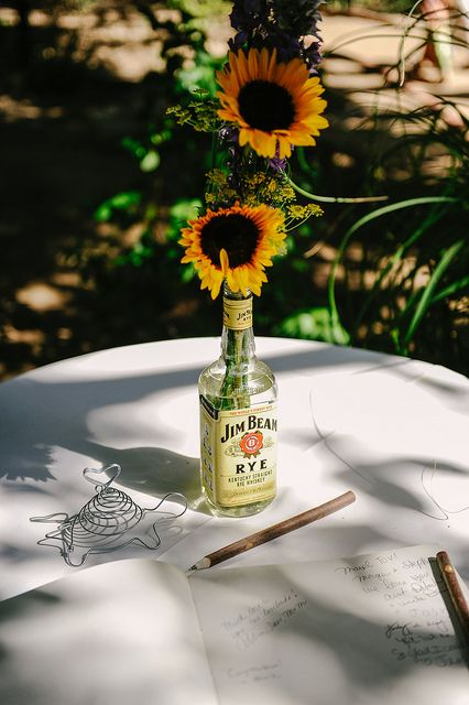 Stephanie & Morgan's whiskey and wildflowers wedding | Offbeat Bride. Simple Centerpieces.