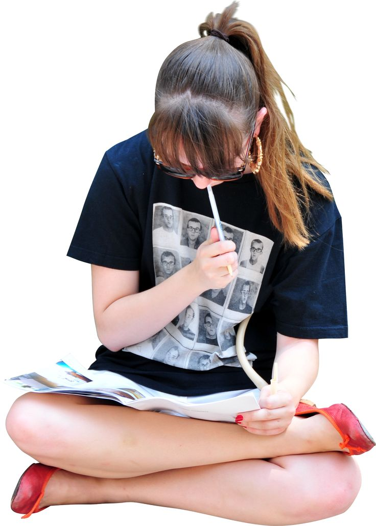 girl sitting on ground, reading and writing