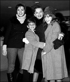 Judy Garland greets her son Joey Luft, 9, and daughter Lorna Luft, 12, after they arrive from California at New York's Kennedy International Airport, Dec. 29, 1964. Garland's elder daughter Liza Minnelli poses with them at left. Minnelli and Lorna Luft both grew up to be singers and actresses, like their mother.
