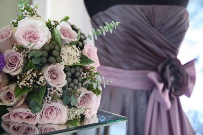 Metalina Roses in the posy bouquet look almost lilac or lavender coloured against this grape and oyster Bridesmaids gown