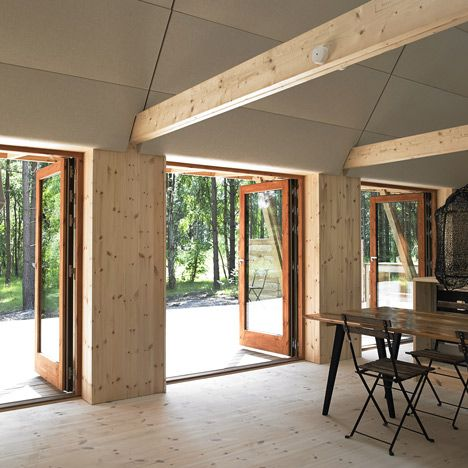 The interior walls of this house are lined with wooden boards, framing a series of rooms intended to house two families. A double-height living room and kitchen forms the centre, while bedrooms are located at the ends and in the loft.