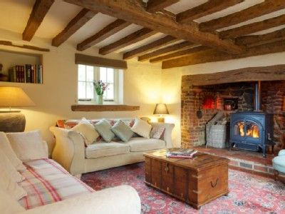 The lounge with woodburning stove set in original inglenook with old bread oven