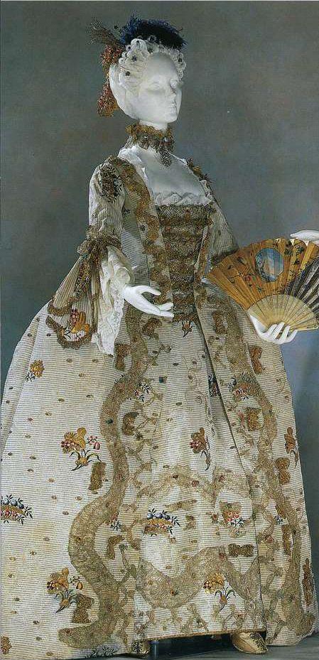 """Придворное платье (robe a la francaise). Около 1760, Англия. Шелковая парча из Спайтфилдза цвета слоновой кости с золотыми, серебряными и полихромными нитями, цветочный орнамент, золотое кружево, серебристый газ, двойные рукава """"пагода"""", нижняя юбка, стомак из золотого и серебряного кружева с оборкой, ангажанты из брюссельского кружева"""