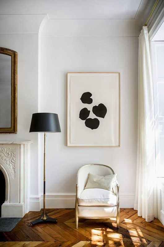 Living room, white chair, painting, black round lamp, light, fireplace, parquet floor