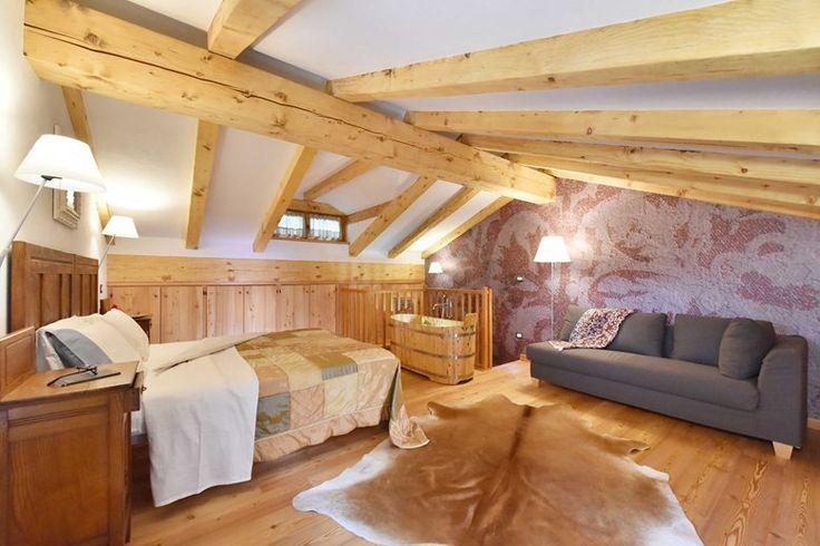 Piano superiore: la suite matrimoniale con salottino, divano letto e vasca da bagno in legno di ginepro. Per l'illuminazione di questo ambiente la nostra proposta sono state le lampade di Luceplan serie costanza e costanzina.
