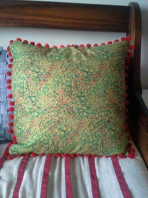 Peacock cushion with pompom trim.