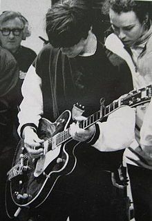 This is a picture of The Stone Roses guitarist John Squire playing live, the long shot conveys the concentration that is within him and portrays him as skillful and talented.