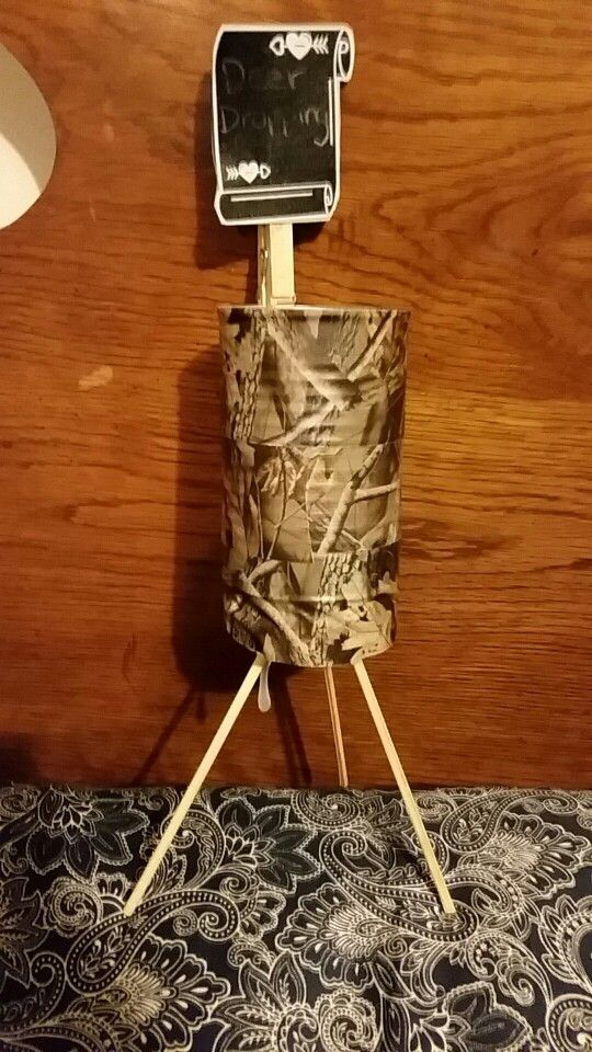 """Deer Feeder Birthday Party Decor Old vegetable cans, covered in camo duct tape. Hit glued styrophoam to the bottom and stuck in legs, secured with more hot glue. Signs are glued to a clothespin the clipped on. This one will hold """"Deer Droppings"""" or chocolate candy!!"""