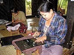 Women etch designs on lacquerware trays at one of small-scale producers at Bagan.