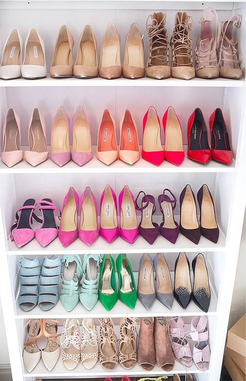 Closet+features+a+tall+white+freestanding+shoe+shelf+filled+with+designer+shoes.
