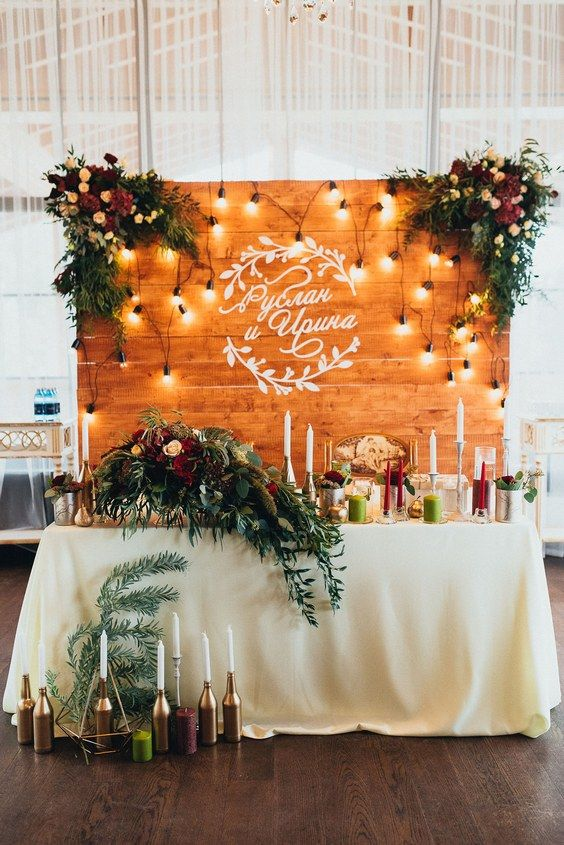 rustic wood backdrop and greenery sweetheart table for indoor wedding reception