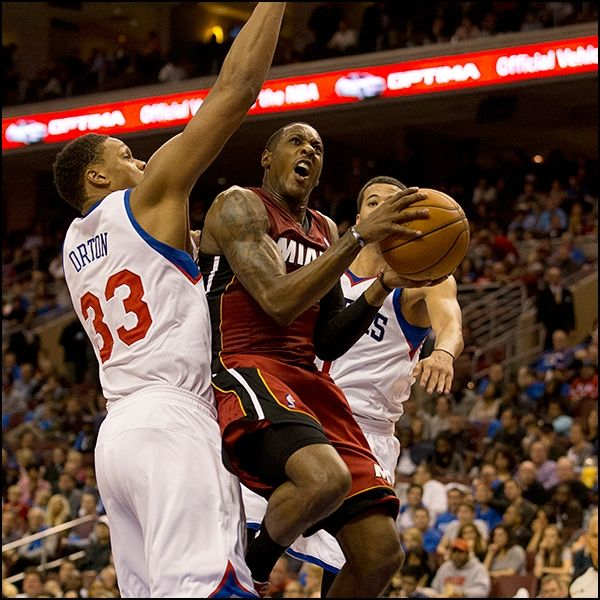 Mario Chalmers absorbs contact from Philadelphia 76ers defenders