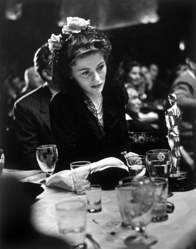 At the 1942 Academy Awards, Joan Fontaine gazes at the Best Actress Oscar she won for her role in Suspicion — an achievement that made her, incredibly, the only actor or actress to ever win an Oscar for a performance in an Alfred Hitchcock film.: Actress Oscar, Oscars, Joan Fontaine, Alfred Hitchcock, Hollywood, Academy Awards, 1942 Academy, Photo, Fontaine Gazes