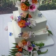 Multicolored floral cascade touches just the corners of this gently turning butter cream wedding cake. Cakes By Graham, More Than Just the Icing on the Cake.  http://richmondcakes.com/