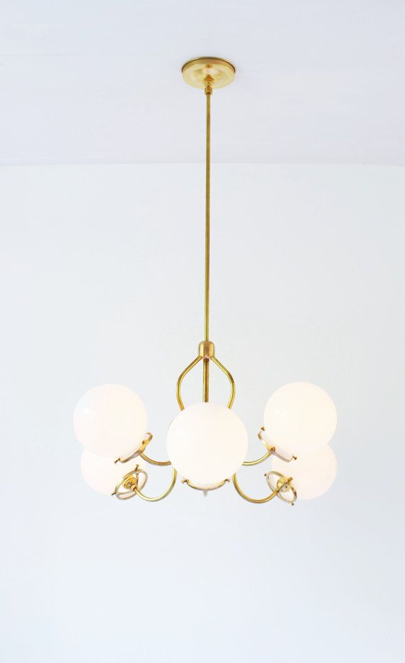 Redecorate your space with style and simplicity.  This new take on a classic brass chandelier with fluted arms is easy to install and features 6 white glass globes to help you make your space glow. Unique and beautiful, this chandelier instantly adds style to any room. Each glass globe measures 6 inches in diameter. Photos show the chandelier with a 24 inch drop rod. Custom hanging lengths are available upon request. The light measures 23 in diameter. Brass ceiling plate is 5 inches in…