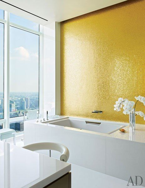 WIFE'S BATH...yes please, separate bathrooms! A wall in the wife's bath is embellished with gold-leafed glass-mosaic tile, and the tub features Dornbracht fittings.