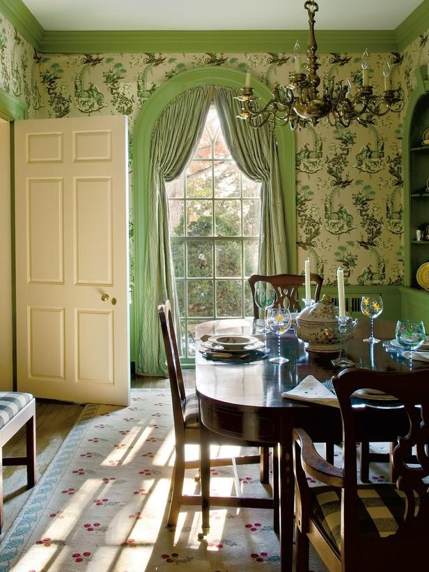 "Trim painted with Farrow  Ball's ""Folly Green"" accentuates the vivid wallpaper in this dining room"