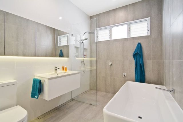 Bathroom walk in shower with large 600x300 concrete look porcelain tiles, louvre windows, underfloor heating and builtin mirrored shaving cabinets
