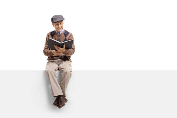 Senior Sitting On A Panel And Reading A Book Stock Photo