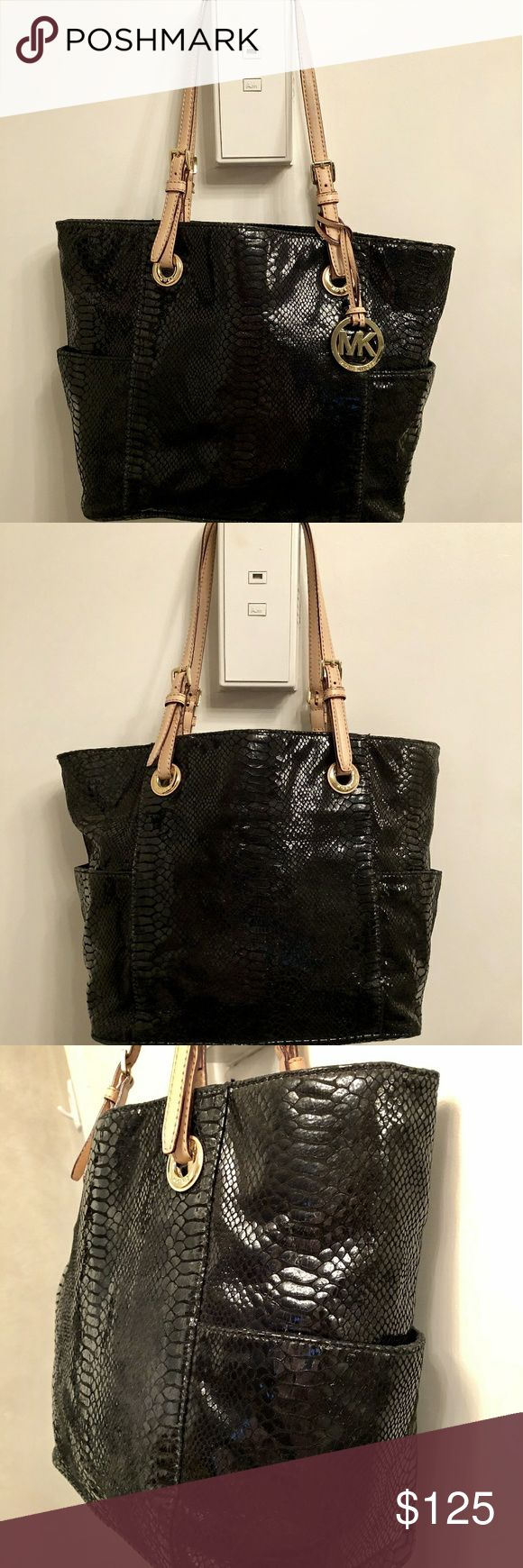 "MICHAEL Michael Kors jet set python leather bag Black python-embossed leather tote bag w/tan dual adjustable shoulder straps. Buckled top handles loop through logo-engraved grommets.Goldtone MK hardware. Sturdy hanging logo fob & 'feet'. Light scratches.Open bag w/interior zip pocket, cell phone pocket etc, 2 exterior side pockets.Logo MK black fabric interior w/factory tag sewn into lining.11""height x 16"" across (top laid flat) / 12"" across (bottom) x 6""width (bottom).Beautiful bag, like…"