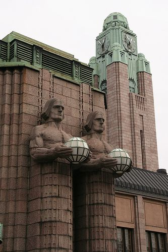 Central train station, Helsinki, Finland. The station building was designed by Eliel Saarinen and inaugurated in 1919. It was chosen as one of the world's most beautiful railway stations by BBC in 2013. The station is mostly clad in Finnish granite, and its distinguishing features are its clock tower and the two pairs of statues holding the spherical lamps, lit at night-time, on either side of the main entrance.