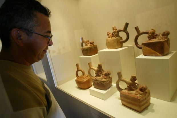 A museum visitor looks at a collection of erotic pottery at the Rafael Larco Herrera Museum in Lima, Peru.
