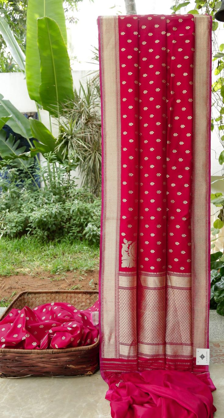 This crimson red Benares silk has silver zari bhuttas all over. The border and pallu have intricately woven silver zari giving it a rich and traditional look.
