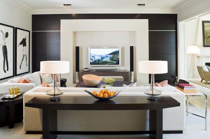 Abbinando elementi classici e moderni, questo salotto emana un senso di relax ed eleganza - arredo con divani color crema e mobili in legno colore marrone scuro - parete rivestita