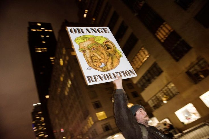 """Homemade signs were peppered throughout the crowd at the """"We Stand United"""" pre-inauguration rally outside Trump International Hotel in Columbus Circle on Jan. 19, 2017."""