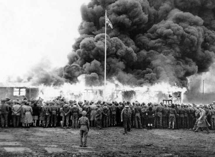 On May 21, Colonel Bird, Commandant of Belsen Camp, gave the order for the last hut at Belsen Concentration Camp to be burned. A rifle salute was fired in honor of the dead, the British flag was run up at the same moment as a flame-thrower set fire to the last hut. A German flag and portrait of Hitler went up in flames inside the hut in June of 1945. (AP Photo/British Official Photo)