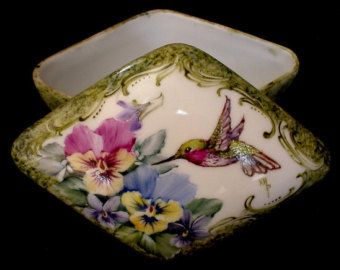 """SOLD...This beautiful hand painted porcelain box measures 4-1/2"""" long x 3-1/4"""" wide x 2"""" deep. Design features a hummingbird flitting among pansies and violets with Victorian style scrolling. This piece is painted entirely by hand. No decals were applied for this decoration and it is signed by myself. $34.50 + $5.59 shipping"""