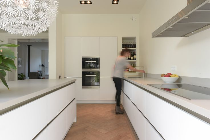 Meters lange strakke moderne witte maatwerk keuken, met een hoge kastenwand met nissen welke rondom gelijk loopt met de gestucte wand. In combinatie met de gerookte eiken visgraad vloer een prachtige stijlvolle en tijdloze leefkeuken. www.pieterdeboer.com