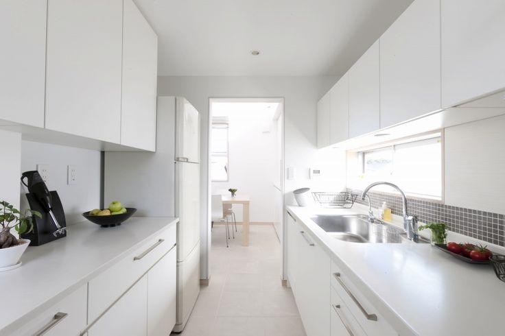 真っ白な扉とカウンターに、グレーのモザイクタイルを効かせたシンプルモダンなⅠ型キッチン。背面のカウンターにも家電類は置かず、美しいキッチンを目指しました。ダイニング・リビングから緩やかに仕切ったクローズドタイプのキッチンですが、2方向にある窓からの光で明るく気持ちよい空間になりました。