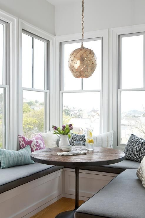 Gorgeous breakfast nook is filled with a U shaped banquette topped with dark gray bench cushions ...
