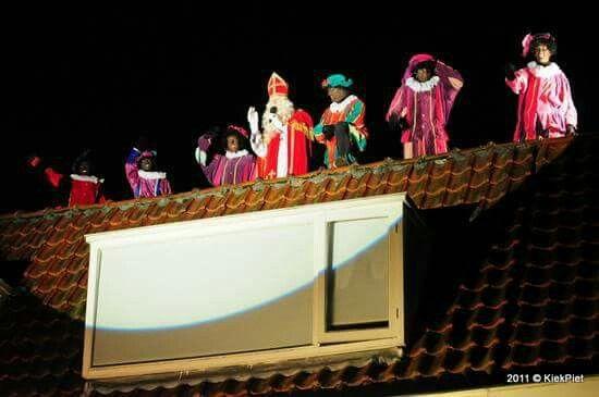 Sinterklaas met zijn Pieten op het dak