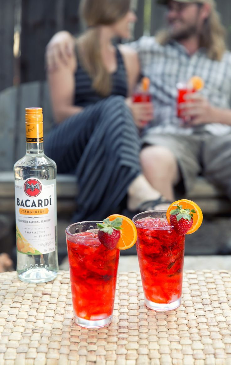Enjoy drinks with friends! These cocktails are so easy to make. Mix some strawberry soda with ice and a shot or two of Bacardí Tangerine Rum. Garnish with strawberries and orange slices.