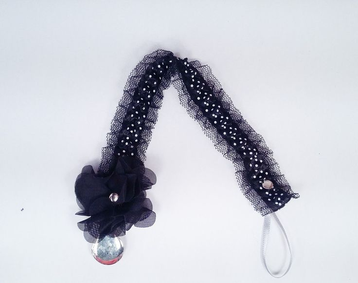 Zawieszka do smoczka z czarnego tiulu w białe kropeczki. Dodatkową ozdobę stanowi czarny kwiatek przy klipsie. Elegancka i gustowna idealna na co dzień jak i na specjalne okazje.